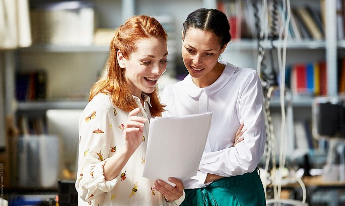two women looking at papers smiling